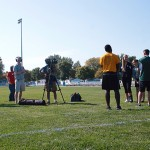 The broadcast crew gathers on the soccer field.